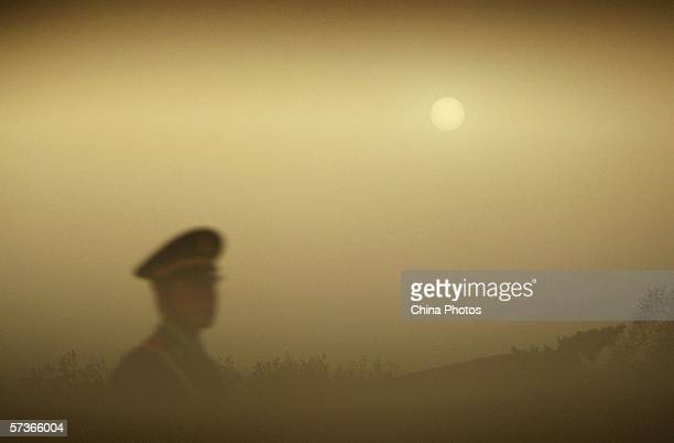A police officer patrols Tiananmen Square during a dust storm on April 18 2006 in Beijing China A sandstorm hitting the ChinaMongolia border on April...