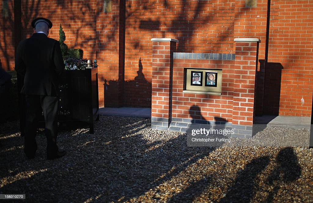 A police officer pauses for thought in the memorial garden dedicated to murdered PC's Fiona Bone and Nicola Hughes, which was unveiled today on December 13, 2012 in Hyde, England. Police Constables Fiona Bone, 32, and her colleague Nicola Hughes, 23, were killed as they responded to what they thought was a routine burglary call in Mottram, Greater Manchester and were murdered in a gun and grenade attack. The memorial garden outside Hyde police station has been created using funds donated by the public, businesses and police partners.
