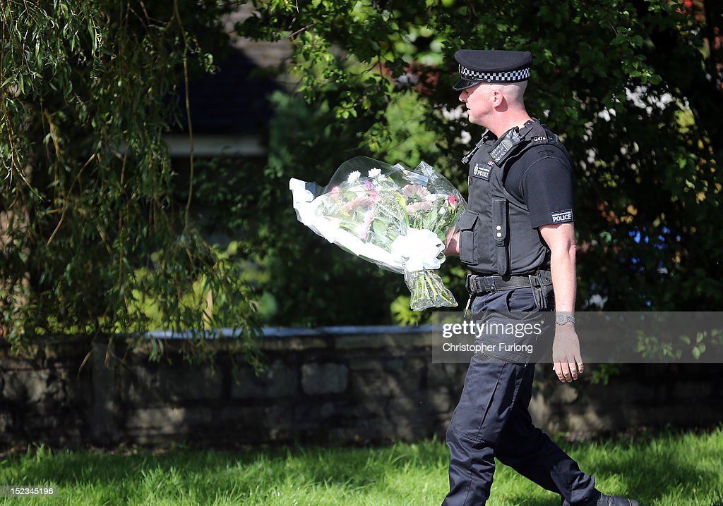 A police officer pays his respects and places floral tributes near to the scene in memory of WPC's Nicola Hughes and Fiona Bone in Hattersley on September 19, 2012 in Manchester, England. Local man Dale Cregan, 29, has been arrested in connection with the shooting of WPC's Nicola Hughes and Fiona Bone, who were killed as they responded to a routine incident at Abbey Gardens in Hattersley shortly before 11am yesterday.