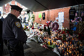 A police officer pays his respects at a memorial where two New York Police Department officers who were shot and killed last Saturday on December 23...