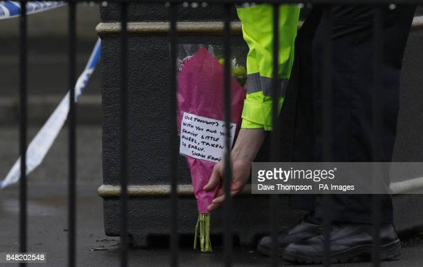 A police officer places flowers inside a cordon close to the scene of a suspected gas blast in Buckley Street in the Shaw area of Oldham Greater...