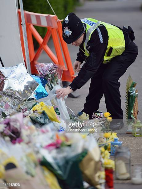 A police officer places flowers on the pavement outside a house in Allerton where a fire claimed the lives of six children on May 14 2012 in Derby...