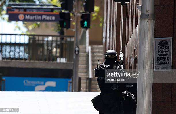 A police officer points his weapon towards the siege at Lindt Cafe in Martin Place on December 15 2014 in Sydney Australia Major landmarks in Sydney...