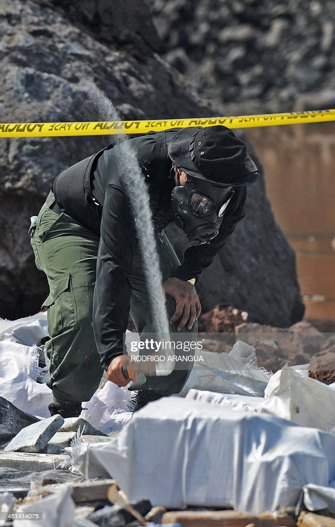 A police officer prepares part of the seized 11,5 tons of cocaine and 298 kg of marijuana to be burnt in Cerro Patacon, near Panama City on November 22, 2013. AFP PHOTO / Rodrigo ARANGUA