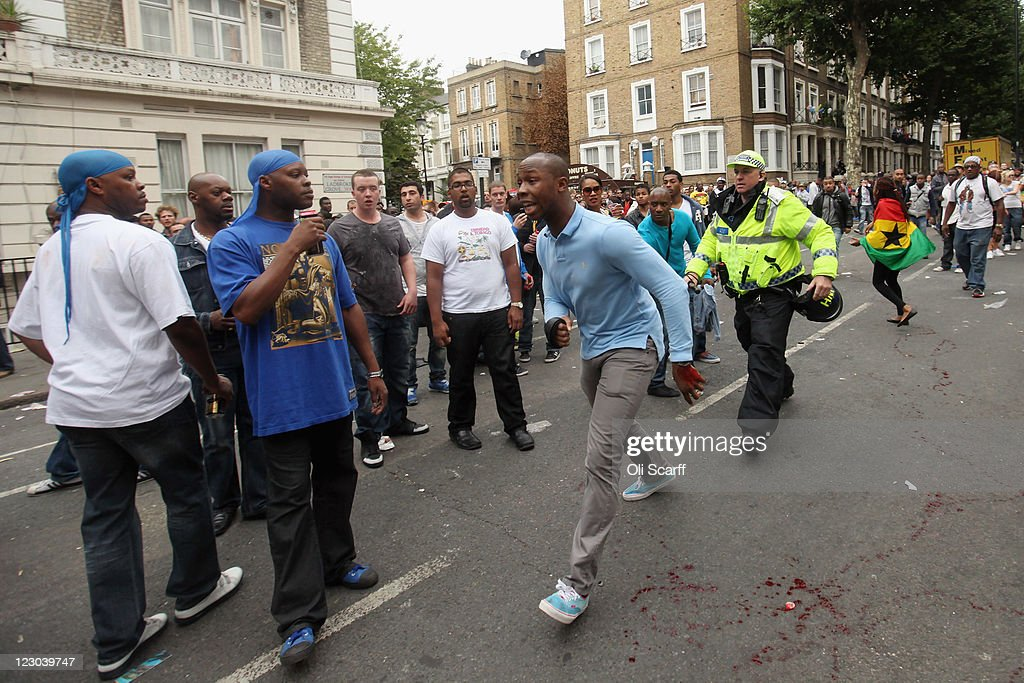 A police officer prepares to apprehend a man (C) near to where a man was stabbed at the Notting Hill Carnival on August 29, 2011 in London, England. The annual carnival, which is the largest of its kind in Europe and is expected to attract around 1 million revellers, has taken place every August Bank Holiday since 1966.