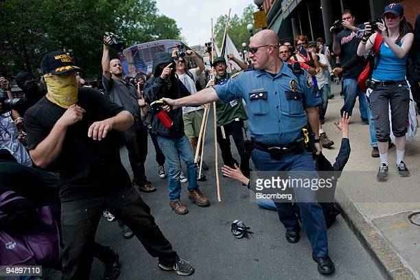 A police officer prepares to fire pepper spray at demonstrators interfering with him making an arrest during a rally from the State Capitol to the...