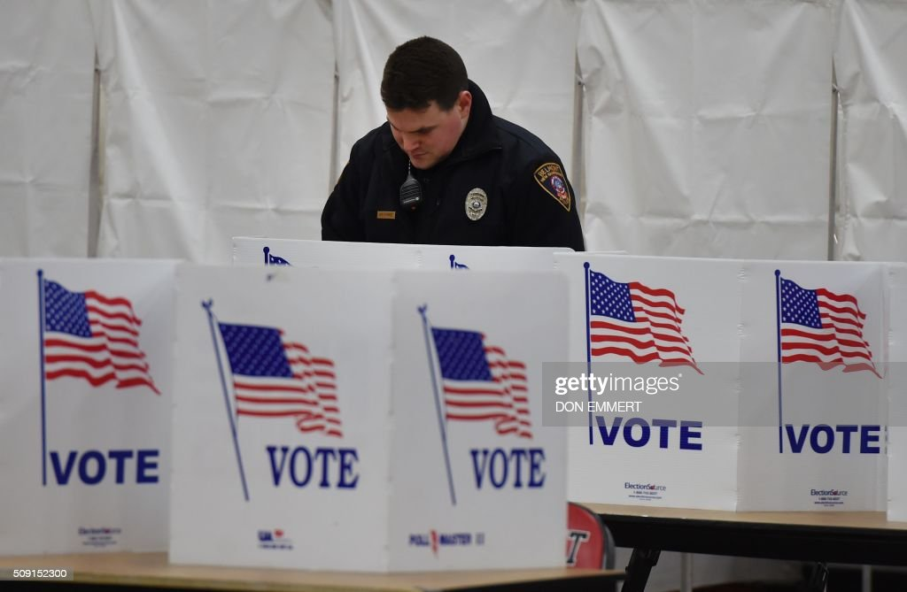 A police officer prepares to vote at Belmont High School February 9, 2016 in Belmont New Hampshire. Voting began in New Hampshire on Tuesday in the first US presidential primary, where Donald Trump leads the packed Republican field and Bernie Sanders was polling ahead of Hillary Clinton. Despite its small size New Hampshire's spot on the electoral calendar gives it special importance in the long state-by-state battle to select the Republican and Democratic candidates who will go head to head for the White House. / AFP / Don EMMERT