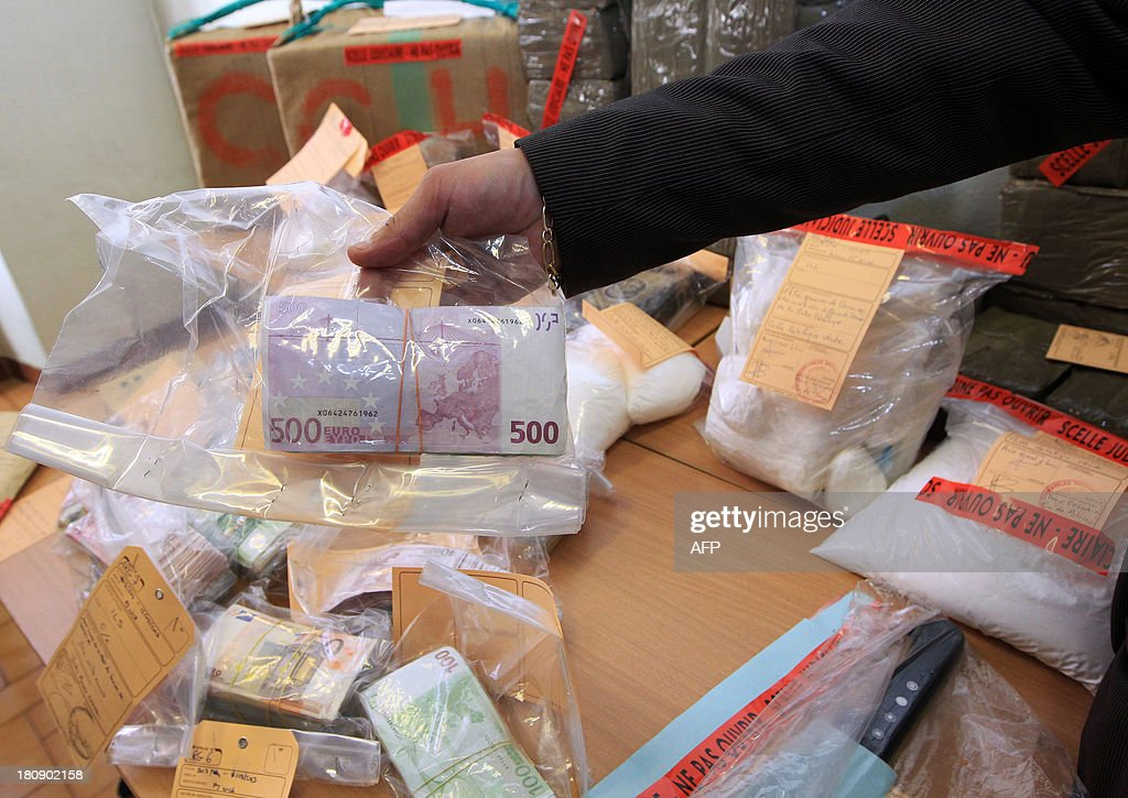 A police officer presents a bundle of cash sized with 4kg of Cocaine, one of heroin and 250kg of cannabis during the dismantling of a drug traffic after an inquiry by the Inter region police direction (DIPJ) of Marseille, on September 17, 2013 in Nice. AFP PHOTO / JEAN CHRISTOPHE MAGNENET