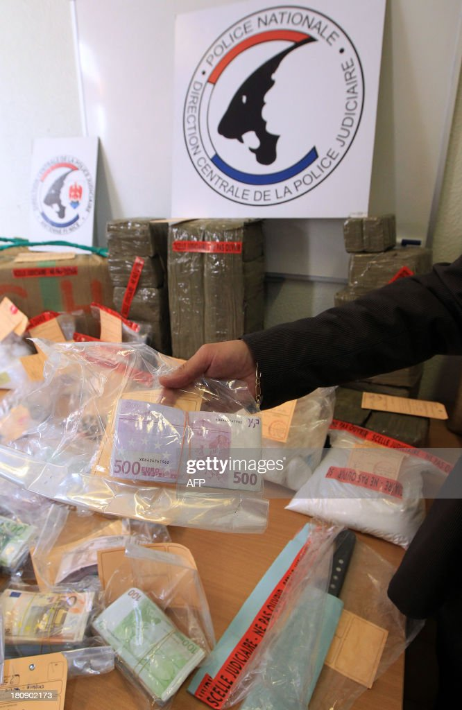 A police officer presents a bundle of cash sized with 4kg of Cocaine, one of heroin and 250kg of cannabis during the dismantling of a drug traffic after an inquiry by the Inter region police direction (DIPJ) of Marseille, on September 17, 2013 in Nice.