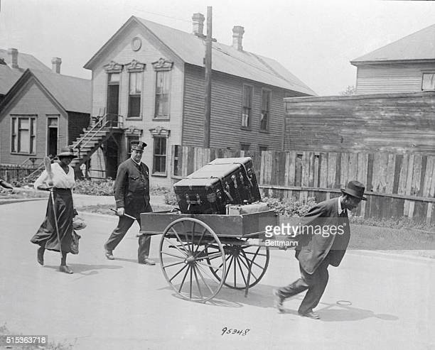 A police officer provides protection to Black residents of the South Side of Chicago moving shortly after the riots of 1919