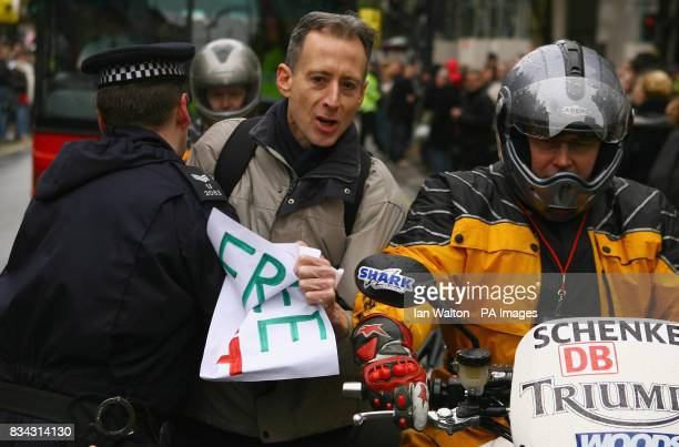 A police officer pushes away human rights activist Peter Tatchell during the relay of the Olympic torch during its journey across London on its way...