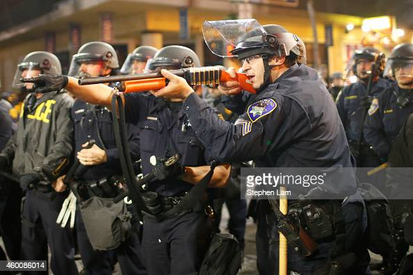 A police officer raises a shotgun toward the crowd during the fourth night of demonstrations over recent grand jury decisions in policeinvolved...