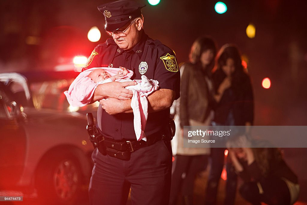 Police officer rescuing a baby : Stock Photo