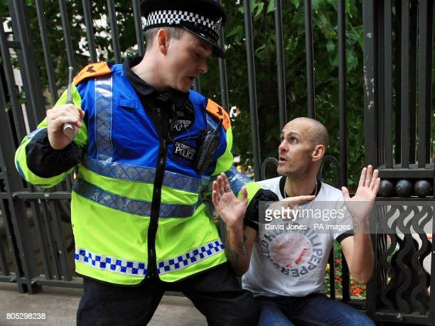 A police officer restrains a man during the English Defence League demonstration in Birmingham