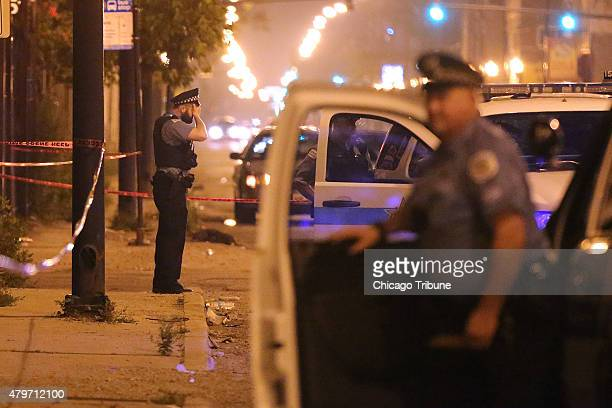 A police officer rests his hand on his forehead at the scene where a 23year old man was shot in the face in the early morning hours Monday July 6...