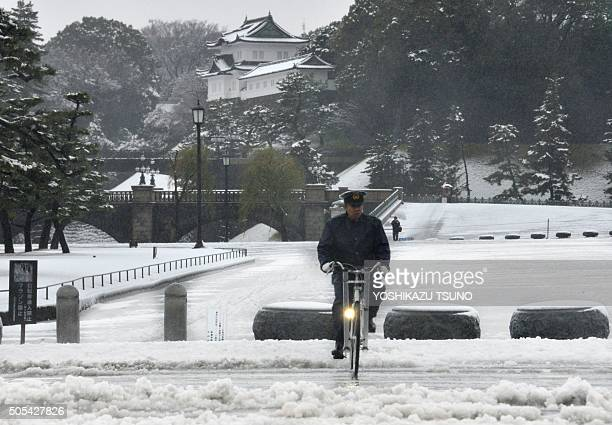 A police officer rides a bicycle on a snow covered field in front of the Imperial Palace in Tokyo on January 18 2016 Heavy snow blanketed Tokyo...