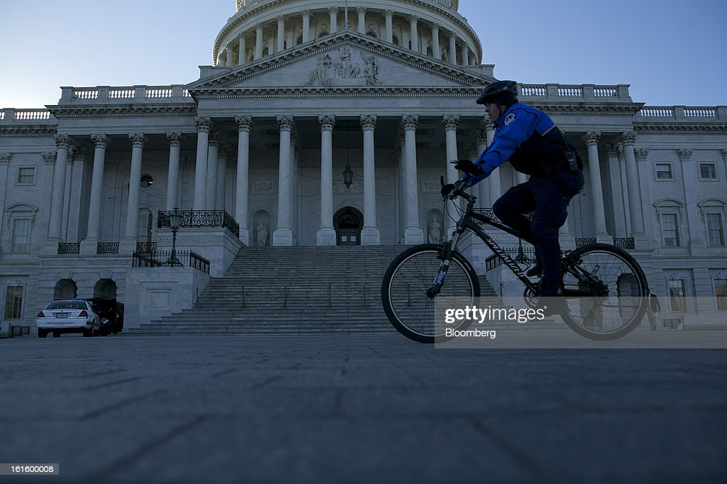 A police officer rides a bicycle past the U.S. Capitol in Washington, D.C., U.S., on Tuesday, Feb. 12, 2013. With a second-term agenda that includes the politically contentious issues of gun control, immigration and climate change, U.S. President Barack Obama's ability to rally the public behind him is tied to the performance of the economy. Photographer: Andrew Harrer/Bloomberg via Getty Images