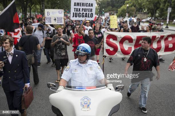 A police officer rides a motorcycle as Juggalos fans of the music group Insane Clown Posse march during a demonstration in Washington DC US on...