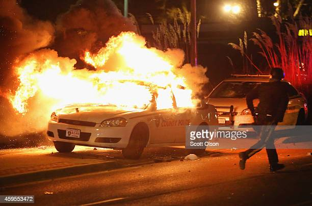A police officer runs from a burning squad car after it was set on fire by demonstrators during a protest following the grand jury announcement on...