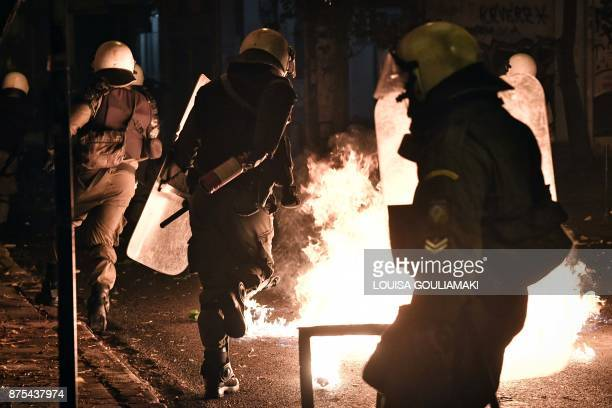 TOPSHOT A police officer runs past fire during clashes with demonstrators on November 17 2017 in Athens following a rally commemorating the 1973...