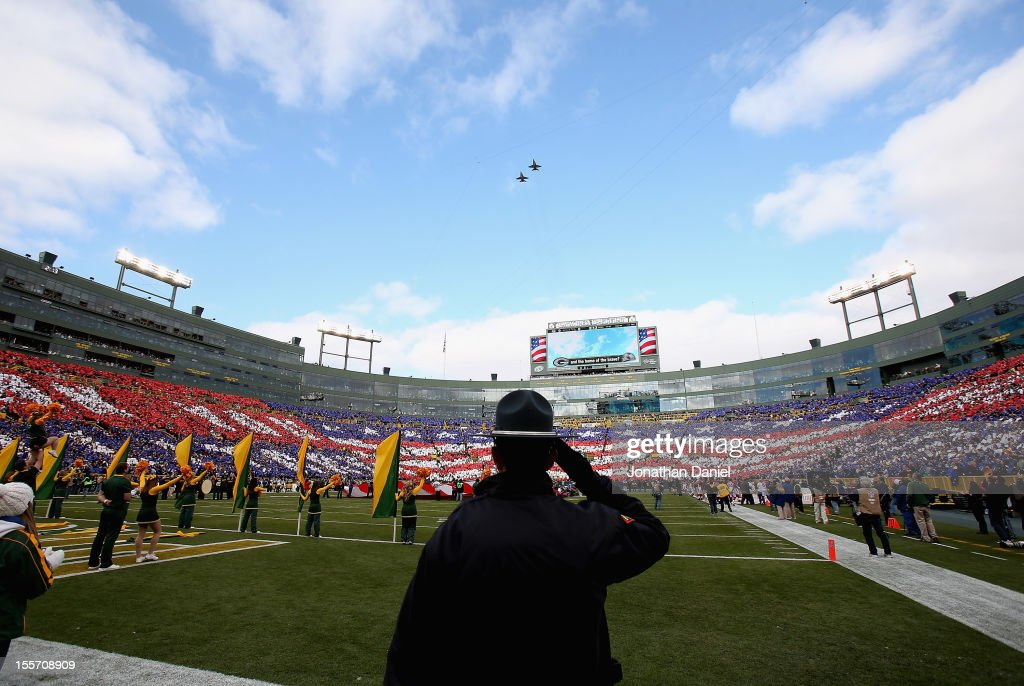 A police officer salutes during the National Anthem before the Green Bay Packers take on the Arizona Cardinals at Lambeau Field on November 4, 2012 in Green Bay, Wisconsin. The Packers defeated the Cardinals 31-17.