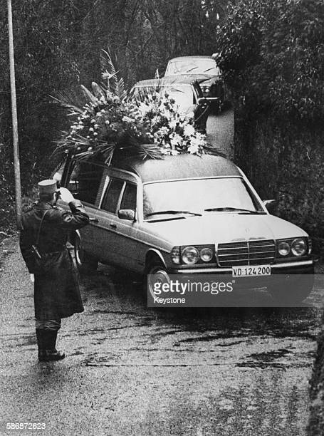 A police officer salutes the hearse carrying the coffin of English film actor and director Charlie Chaplin at Chaplin's funeral CorsiersurVevey...