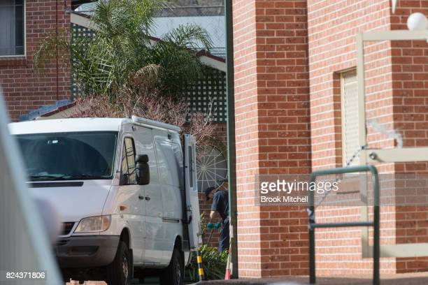 A police officer searches a garden bed of an apartment complex in Sproule Street Lakemba the scene of an overnight terror raid on July 30 2017 in...