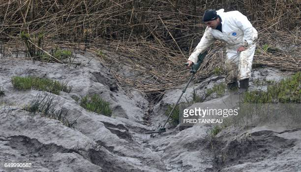 A police officer searches on March 9 2017 on the swampy bank of the river Aulne near the Caouissin's house in PontdeBuislèsQuimerch western of France...