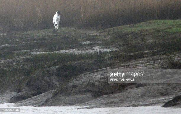 A police officer searches the area on March 8 2017 in PontdeBuis western France after the brotherinlaw of a Frenchman who went missing with his wife...