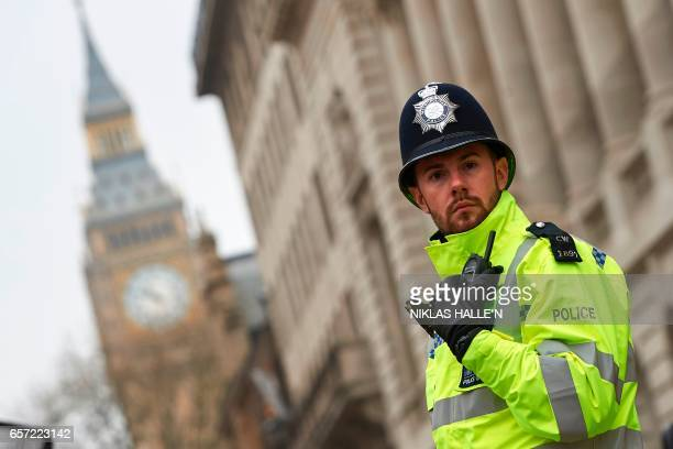 A police officer secures a street leading to the Houses of Parliament in central London on March 24 2017 two days after the March 22 terror attack on...