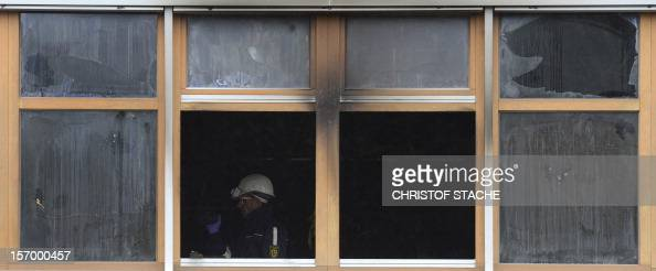 A police officer secures evidence at the burnt out workshop for disabled people in TitiseeNeustadt southern Germany on November 27 2012 Experts...
