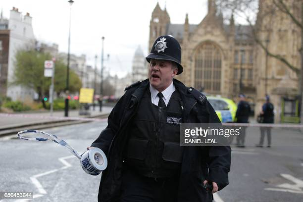 A police officer sets up a police cordon outside the Houses of Parliament in central London on March 22 2017 during an emergency incident / AFP PHOTO...