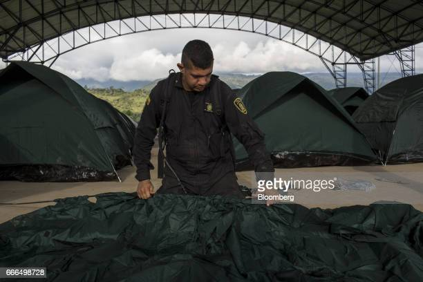 A police officer sets up tents at a disaster relief center after landslides in Mocoa Putumayo Colombia on Monday April 3 2017 Torrential rains caused...