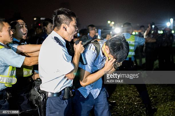 A police officer shouts at a prodemocracy protester after he was hit with pepper spray in Hong Kong on October 15 2014 Hong Kong has been plunged...