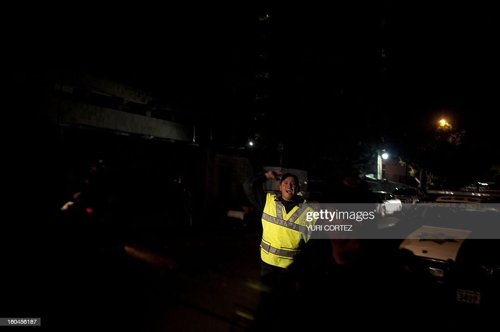 A police officer shouts to the press during an alleged bombing alert at the headquarters of state-owned Mexican oil giant Pemex in Mexico City on January 31, 2013, following a blast inside the building. An explosion rocked the skyscraper, leaving up to 25 dead and 101 injured, as a plume of black smoke billowed from the 54-floor tower, according to official sources.