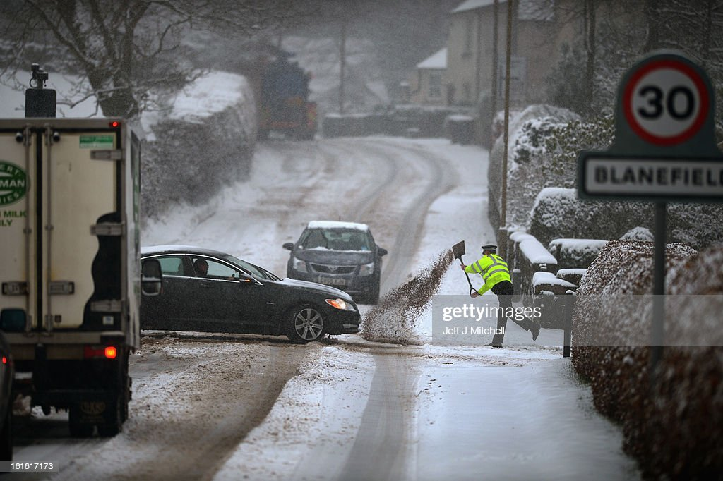 A police officer shovels salt onto the road to help on February 13, 2013 in Blanefield, Scotland. Weather forecaster have issued a yellow weather warning of up to 10cm of snow on higher routes, with the possibility of travel disruption.
