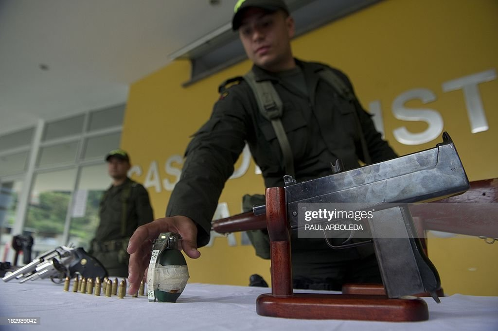 A police officer shows a hand granade during a press conference at the Justice House (sort of police station) of the Commune 13 -- one of the shantytowns with the highest rates of urban violence and displacementon -- on March 1, 2013, in Medellin, Antioquia department, Colombia. The Colombian police confiscated to 13 guns and a hand granade to criminal gangs during an operation, officials said. So far this year, more than 105 people have been killed by urban conflict and 335 people displaced, due to disputes between gangs for the control of the territory. Violent street gangs have 'invisible borders' that delineate their territories in Medellin, ranked as the 14th most dangerous city in the world with a murder rate of 70 per 100,000 inhabitants in 2011. AFP PHOTO/Raul ARBOLEDA