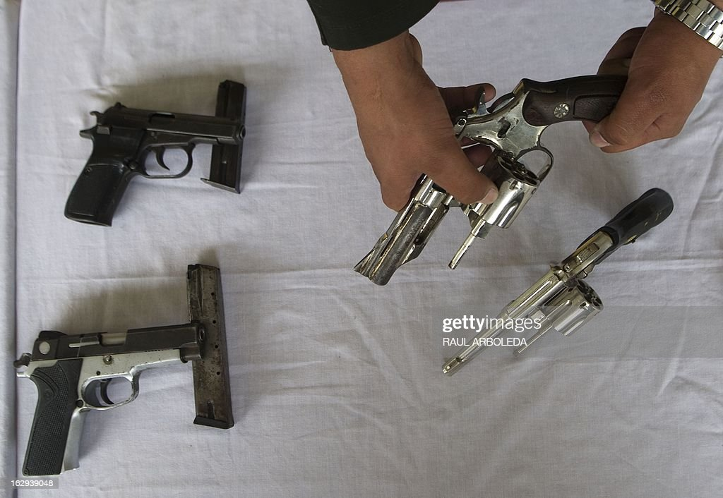 A police officer shows guns during a press conference at the Justice House (sort of police station) of the Commune 13 -- one of the shantytowns with the highest rates of urban violence and displacementon -- on March 1, 2013, in Medellin, Antioquia department, Colombia. The Colombian police confiscated to 13 guns and a hand granade to criminal gangs during an operation, officials said. So far this year, more than 105 people have been killed by urban conflict and 335 people displaced, due to disputes between gangs for the control of the territory. Violent street gangs have 'invisible borders' that delineate their territories in Medellin, ranked as the 14th most dangerous city in the world with a murder rate of 70 per 100,000 inhabitants in 2011. AFP PHOTO/Raul ARBOLEDA