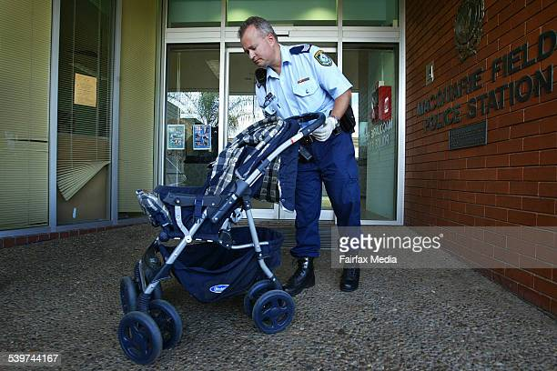 A NSW police officer shows the pram that was used in an incident which a gang of boys who bashed a dog to death in a Reserve between Saluana Way and...