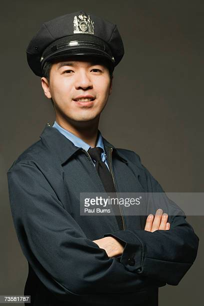 Police officer smiling, on a black background, portrait