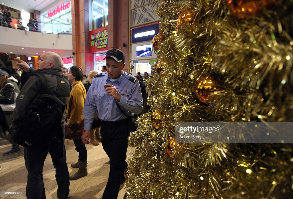 A police officer speaks on a walkie-talkie to help maintain crowd control during Christmas shopping at a shopping mall on December 8, 2012 in Berlin, Germany. German consumer confidence dropped prior to the Christmas season from a high level, according to a survey released at the end of November, expecting to harm retail sales in December, but not to the point of hurting businesses greatly.