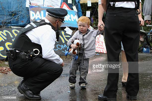 A police officer speaks to a child resident of the Dale Farm travellers' settlement at the camp's entrance on the night before the eviction on...