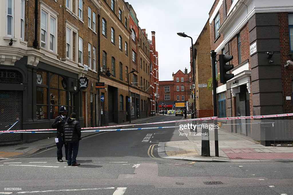 A police officer speaks to a man outside a cordon off section of Bayham street, Greenland street and Greenland Place as a murder investigation is underway in Camden on May 29, 2016 in London, England. Reportedly a stabbing took place in the area leaving one man dead after being taken to the hospital.