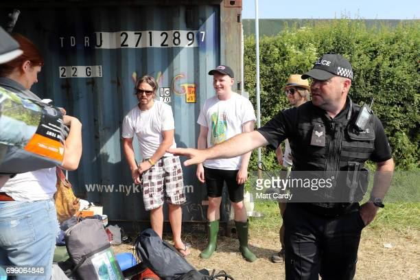 A police officer speaks to festival goers as the gates open at the Glastonbury Festival amid heightened security at Worthy Farm in Pilton on June 21...