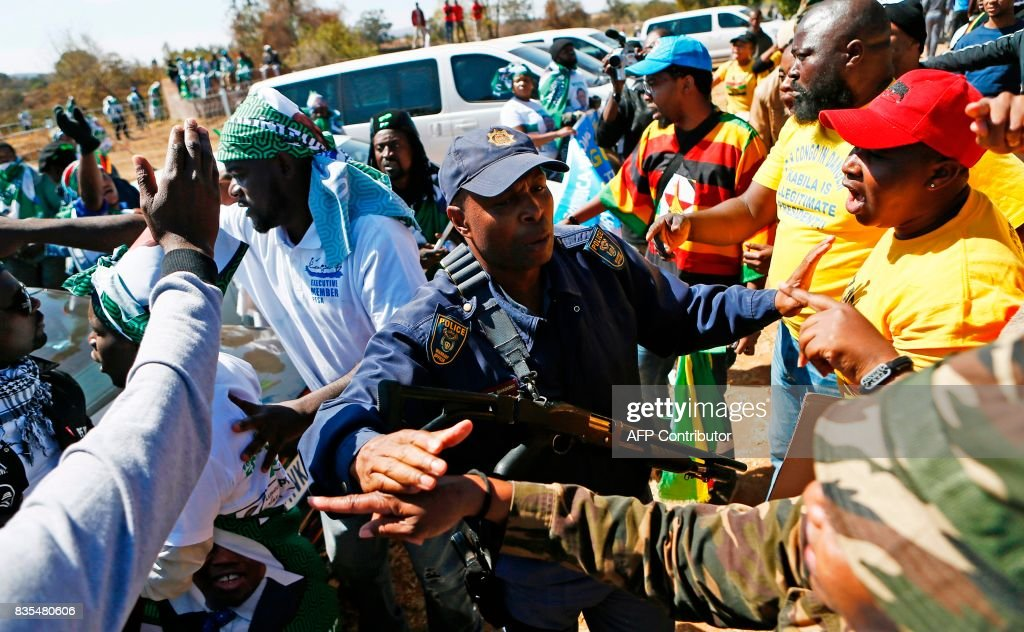 A police officer speaks with protesters from various Southern African Development Community (SADC) countries as they demonstrate near the entrance to Department of International Relations and Cooperation where the SADC Summit is being held in Pretoria on August 19, 2017. The protesters are demanding for the Democratic Republic of Congo (DRC) President Joseph Kabila to step down, and also calling on South Africa to set an example in the handling of the Zimbabwe's first lady Grace Mugabe who is seeking diplomatic immunity for an alleged assault in South Africa on a a 20-year-old model. / AFP PHOTO / Phill Magakoe