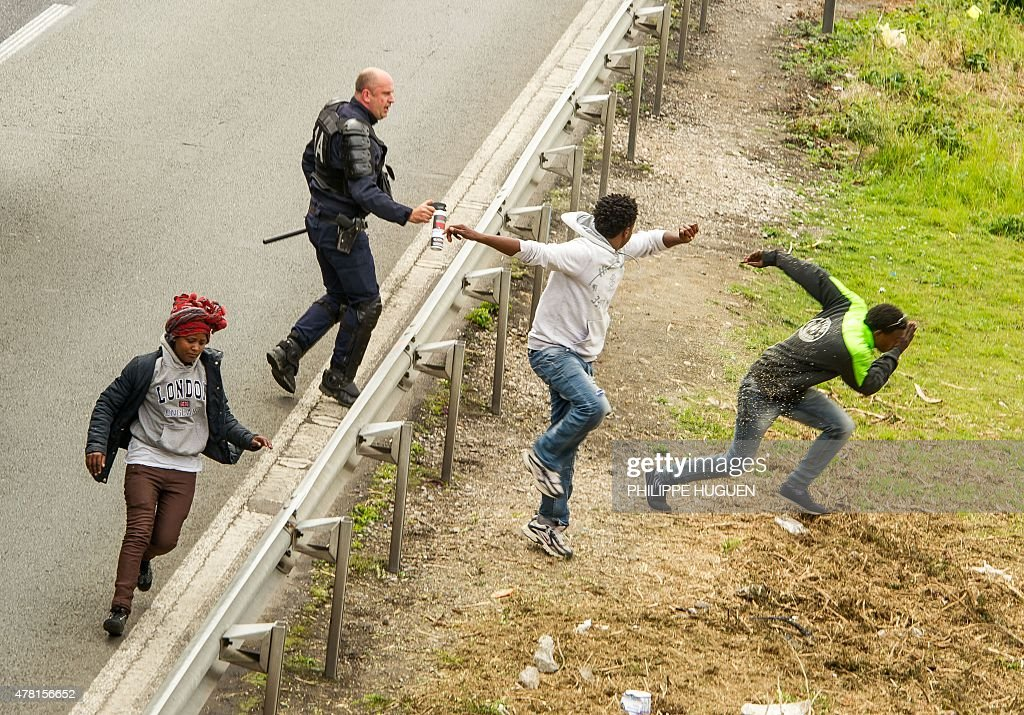 A police officer sprays tear gas to migrants trying to access the Channel Tunnel on the A16 highway on June 23, 2015 in Calais, northern France.