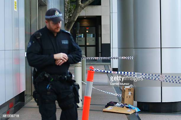 Police officer stand guard next to a suspicious package at the front entrance of the Australian Federal Police headquarters on July 20 2015 in Sydney...