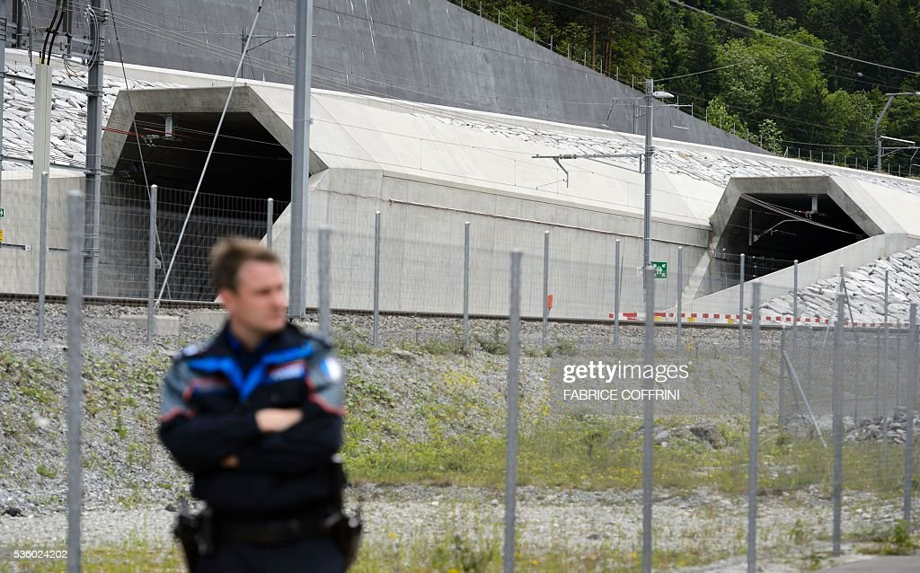 A police officer stand guards the north entrance of the new Gotthard Base Tunnel the world's longest train tunnel on the eve of its opening ceremony on May 31, 2016 in Erstfeld. The new Gotthard Base Tunnel (GBT) is set to become the world's longest railway tunnel when it opens on June 1. The 57-kilometre (35.4-mile) tunnel, which runs under the Alps, was first conceived in sketch-form in 1947 but its construction only began 17 years ago. / AFP / FABRICE