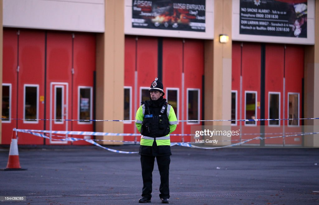 A police officer stand outside Ely Fire Station where a 32-year-old woman was killed in a hit-and-run collision yesterday on October 20, 2012 in Cardiff, Wales. Detectives are questioning a 31-year-old man arrested on suspicion of murder after a series of hit-and-runs in Cardiff that left a woman dead and 13 people injured. Nine casualties, five of them children, are still in hospital, with two adults in critical but stable conditions.