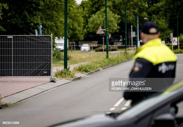 A police officer stands at De Kronkels industrial estate on June 5 2017 after the body of a 14yearold girl was found in a ditch on the edge of the...